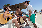 Young men playing music on the Tayelet (beach promenade), Tel-Aviv, Israel
