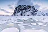 Snowy peaks and ice frame the typical fishermen houses called Rorbu, Eggum, Vestvagoy (Vest-Vagoy) Island, Lofoten Islands, Arctic, Norway, Scandinavia, Europe