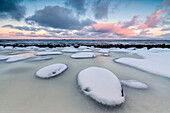 Dawn on the cold sea surrounded by snowy rocks shaped by wind and ice at Eggum, Vestvagoy (Vest-Vagoy) Island, Lofoten Islands, Arctic, Norway, Scandinavia, Europe