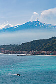 Small boat passing the awe inspiring Mount Etna, UNESCO World Heritage Site, and Europe's tallest active volcano, with Giardini Naxos, Sicily, Italy, Mediterranean, Europe