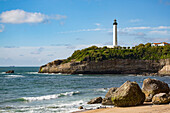 Rocks on the sandy beach and the lighthouse in Biarritz, Pyrenees Atlantiques, Aquitaine, France, Europe