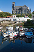 Small port with traditional fishing boats and Eglise Sainte Eugenie in Biarritz, Pyrenees Atlantiques, Aquitaine, France, Europe