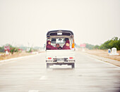 Buddhist monks travelling in the back of a pick up on a modern highway, Myanmar (Burma), Asia