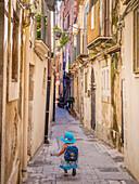 Little girl heading down a narrow Sicilian lane, Syracuse, Sicily, Italy, Europe