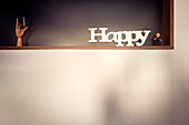 Shelf with wooden hand, toy figure and 'Happy' text