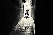 Backlit silhouette of unrecognizable man walking in an alley of the Medina, with some boxes in his hand. Fez, Morocco