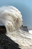 Huge waves crash against the harbour wall at Porthcawl, Bridgend, Wales, UK.