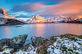The pink sky at sunrise illuminates Reine village with its cold sea and the snowy peaks. Lofoten Islands Northern Norway Europe.