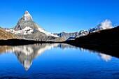 Hikers admire the Matterhorn reflected in Lake Stellisee Zermatt Canton of Valais Pennine Alps Switzerland Europe.