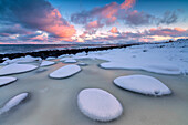 Dawn on the cold sea surrounded by snowy rocks shaped by wind and ice at Eggum Vestvagøy Island Lofoten Islands Norway Europe.