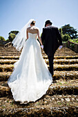 Bride, groom, matrimony, matrimonial, getting, married, just married, together, walk, walking, up, stairs, staircase, Italy, Italian, gown, wedding day, newlyweds, lifestyle, bridal