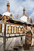 Tibetan pilgrim by prayer wheels and stupas in Lhasa, Tibet.