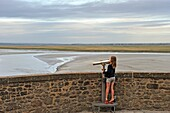 little girl looking through telescope, Mont-Saint-Michel bay, Manche department, Normandy region, France, Europe.