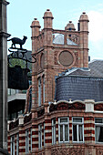 Traditional red brick mixed use building with tower, corner Young street and Kensington High Street, Kensington, London, Great Britain