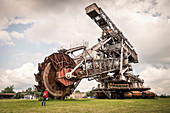 woman in front of bucket-wheel excavator ''Big Wheel'' at Ferropolis - City of Iron, Dessau, Saxony-Anhalt, European Route of Industrial Culture
