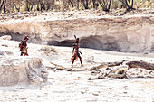 Two Himba women, one of them carrying her child, searching their cattle in a dry riverbed, Kunene, Namibia