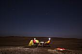 Two men camping under the stars in Damaraland, Kunene, Namibia