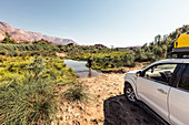 Before crossing the Ugab river from Kunenen to Erongo, the driver checks the water depth. In the Background the Brandberg mountain, Erongo, Damaraland, Namibia, Africa