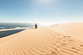 A couple in the dunes high above the lagoons of Sandwich Harbour, Walvis Bay, Erongo, Namibia, Africa