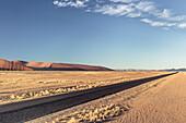 Road between the dunes of Sossusvlei, Namib Naukluft National Park, Hardap, Namibia, Africa.