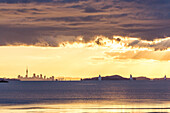 Auckland's skyline seen from Waiheke Island, dramatic sky, Hauraki Gulf, North Island, New Zealand