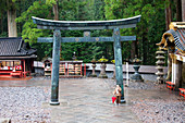 Old monk with red umbrella standing at Torii of Toshogu-Shrine, Nikko, Tochigi Prefecture, Japan