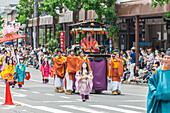 High rank woman in hand carriage pulled by young men and followed by girls in kimono during Festival Aoi Matsuri in Kyoto, Japan