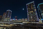 Train tracks of Tokyo Station with skyscrapers during full moon, Chuo-ku, Tokyo, Japan