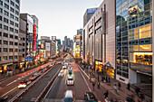 Koshu Kaido Street with Park Hyatt, billboards and moving cars at blue hour, Shinjuku, Tokyo, Japan