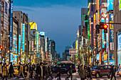 Illuminated signboards and pedestrians crossing Chuo-Dori in Akihabara at night, Chiyoda-ku, Tokyo, Japan