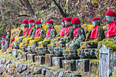 Jizo figures decorated with red knitted caps in Nikko, Tochigi Prefecture, Japan