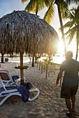 Sonnenuntergang am Salines Strand des Club Med, wo man Hütten, Stühle mieten kann, Wasserski, Windsurfen und den Sonnenuntergang auf dem Dock genießen, mit Blick auf die Palmen.
