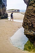 Female solo traveler at Beach of the Cathedrals Natural Monument at Ribadeo municipality, Lugo province, Galicia, Spain, Europe.