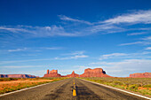 One of the most famous images of the Monument Valley is the long straight road (US 163)leading across flat desert towards sandstone buttes and pinnacles rock. Monument Valley Tribal Park, Nabajo Nation, Arizona/Utah, USA.