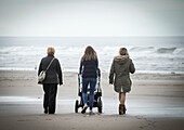 Woman walking on beach with baby in pushchair on a cold and grey day at Saltburn by the Sea, North Yorkshire, England. United Kingdom.