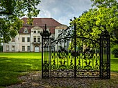 An old solitary wrought-iron locked gate in front of an abandoned baroque manor house in Mecklenburg-Pomerania, Germany, standing in a park environment.