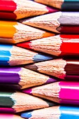 Colouring in pencils interlinked in a closeup macro still life photo. Colors entwined.