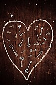 Metal heart keys scattered in chalk heart drawn on wooden background above. Casting love spells.
