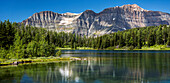 'Panorama of mountain range reflecting off an alpine lake with blue sky; Banff, Alberta, Canada'