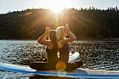 'Fitness models doing yoga on a paddleboard on Pinecrest Lake; California, United States of America'