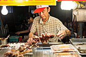 'Local night markets of Taipei are really famous because it's delicious food, a male vendor preparing his specialty food; Taiwan, China'