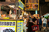 'Local night markets of Taipei are really famous because it's delicious food, a youjng woman enjoying some snacks; Taipei, Taiwan, China'