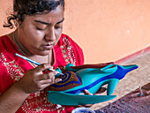 Woman painting a colorful carved wooden figure (alebrije) of a wolf, Oaxaca area, Mexico, North America