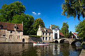 Tourist boat, at the Minnewater Lake and Begijnhof Bridge with entrance to Beguinage, Bruges, Belgium, Europe