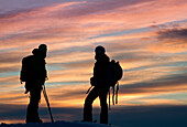 Europe, Italy, Lombardy, Two trekkers, in the sunset, after a journey spent on the mountains