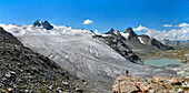 Trekker admire Rutor glacier, close to Deffeyes refuge, Grand Assaly summit on background, La Thuile valley, Aosta Valley, Italy, Europe