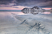 Pink sky on Skagsanden beach surrounded by snow covered mountains reflected in the cold sea, Lofoten Islands Norway Europe