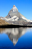 Hikers admire the Matterhorn reflected in Lake Stellisee Zermatt Canton of Valais Pennine Alps Switzerland Europe