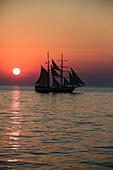 A tall ship sailing in the Aegean Sea while the sun is setting Santorini Cyclades Greece Europe