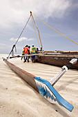 Fishermen trying to place the boat on wood blocks at the low sea level, Jambiani, Zanzibar Island, Zanzibar Archipelago,Tanzania, East Africa.